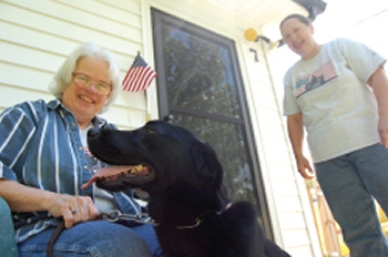 WLM - Linda Hyland receives delivery of Feather, 3, a black Labrador retriever from Cindie Brodie.